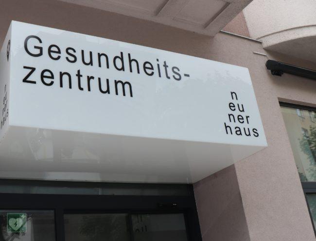 Eingangsbereich des neunerhaus mit Schriftzug Gesundheitszentrum