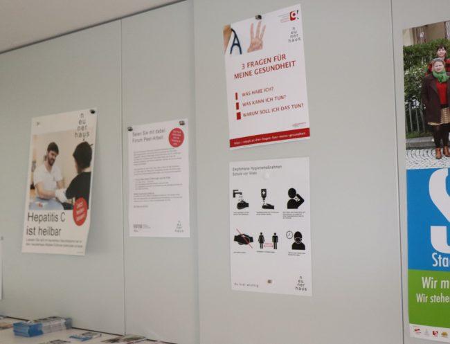 """Poster im Wartebereich des neunerhaus, darunter auch die ÖPGK-Initiative """"3 Fragen für meine Gesundheit"""""""