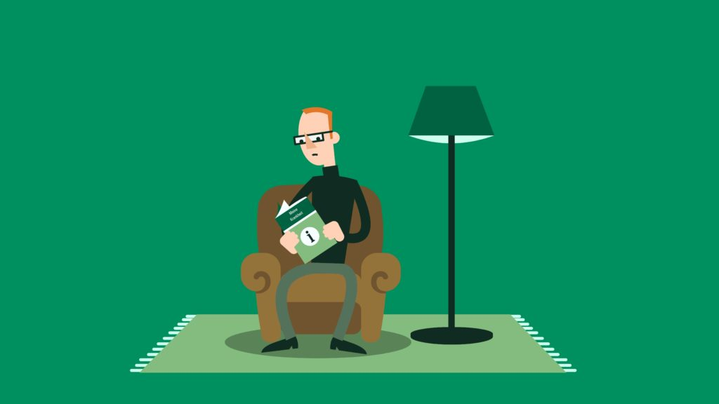 Ein sitzender Man mit einer Broschüre in der Hand.
